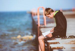 Jugendlicher in gebeugter Haltung beim Lesen